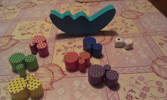 "The contents of the box - One ""Tipping Moon"", 6 different color sets each with three circular pieces of different sizes and two dice with each of the colors shown on each of its sides."