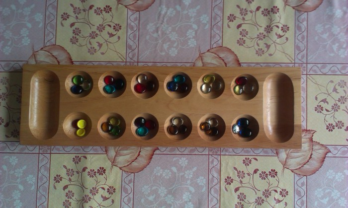"A Mancala board set up for play (with three ""connect four"" pieces used to make up for three missing dragon drops)"